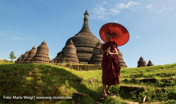 Mönch mit rotem Schirm vor der Ratanabon-Pagode