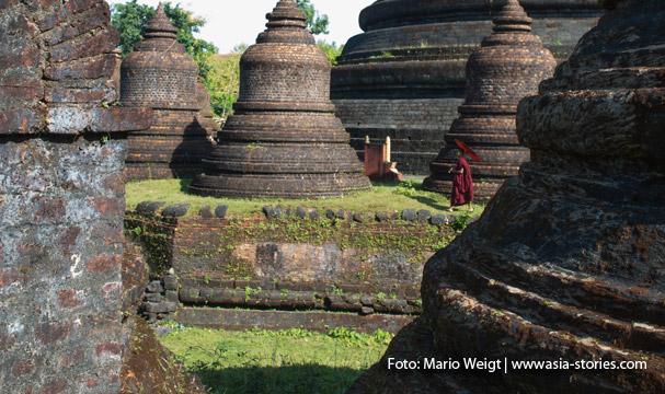 Mrauk U: Mönch mit rotem Bambusschirm in Tempel Htukkant