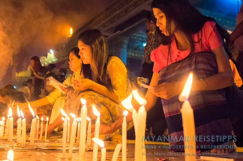 Myanmar Reisetipps | Goldener Felsen Kyaikhtiyo | Frauen stellen in der Nähe vom Goldenen Felsen Kerzen auf.