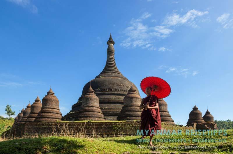 Myanmar Reisetipps | Mrauk U | Mönch mit rotem Schirm vor der Ratanabon-Pagode