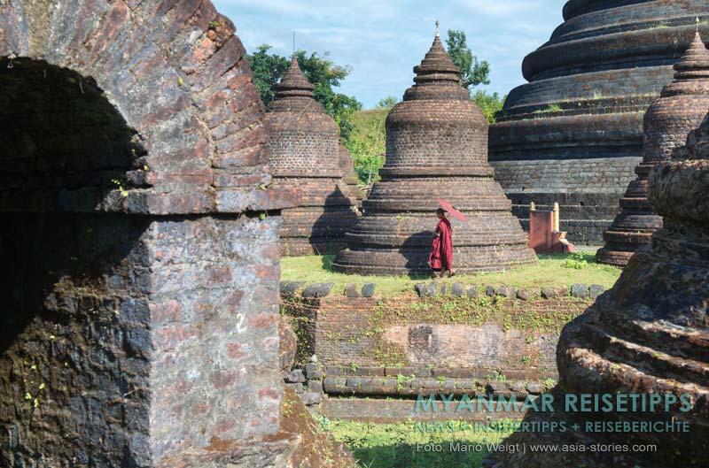 Myanmar Reisetipps | Mrauk U | Mönch mit rotem Bambusschirm am Tempel Ratanabon