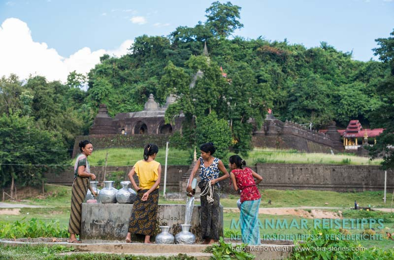 Myanmar Reisetipps | Mrauk U | Frauen beim Wasserholen mit den für Mrauk U typischen Aluminiumgefäßen